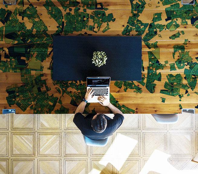 Mann sitzt mit Notebook an Schreibtisch, Im Hintergrund eine Karte